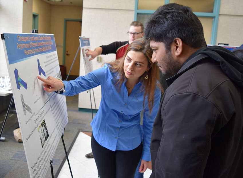person presenting her research poster